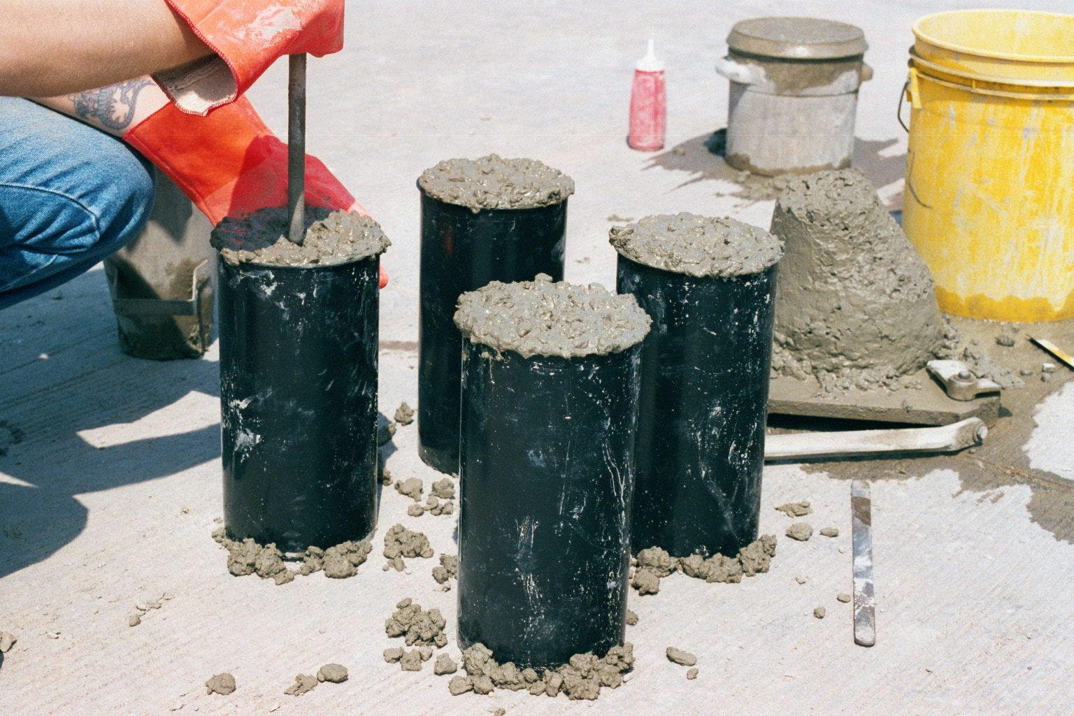A construction worker is creating concrete samples to test.