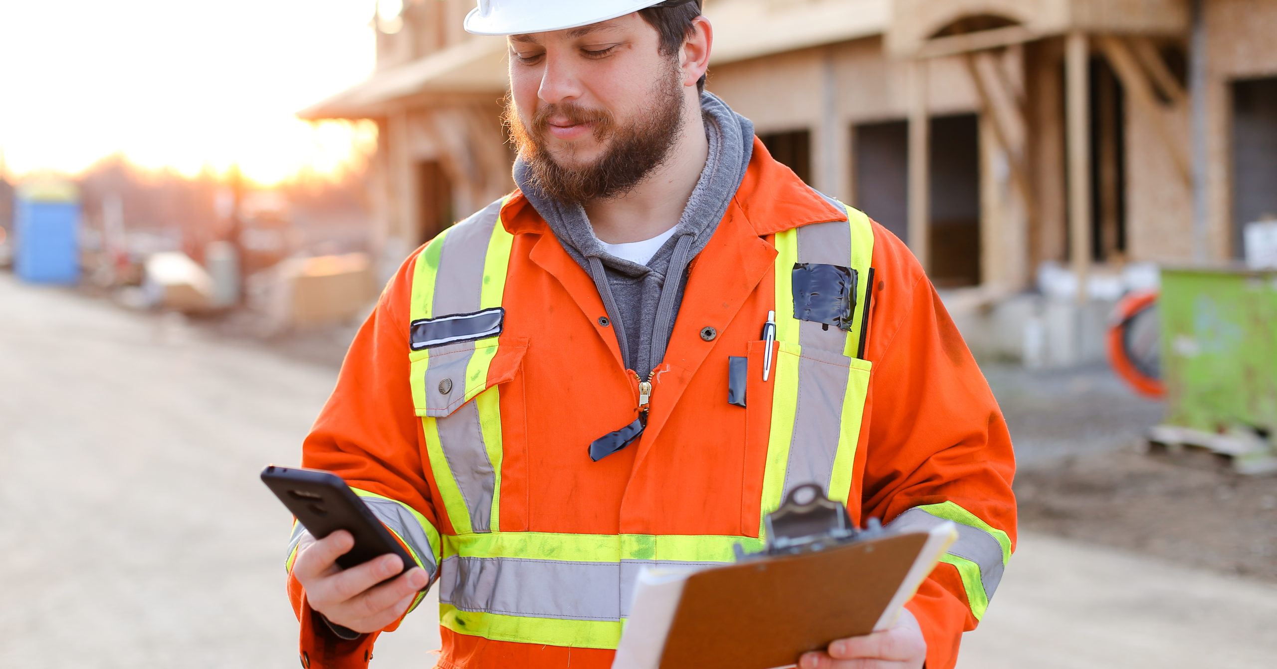A builder is holding and looking at a smart phone in his right hand while holding a clipboard in his other hand.